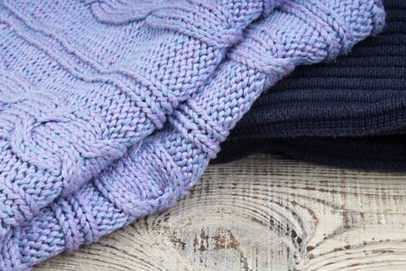 Knitted wool sweaters. Pile of knitted winter clothes on wooden background, sweaters, knitwear, space for text.