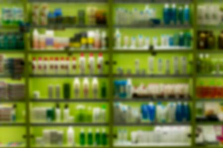 Blur image rows of hair care products on display at store. Cosmetic Products For Sale In Beauty Department store abstract background.
