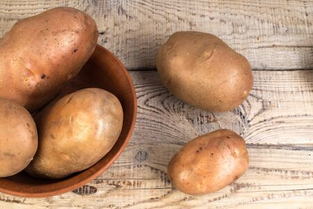 Organic vegan food. potato on wooden background. country style.