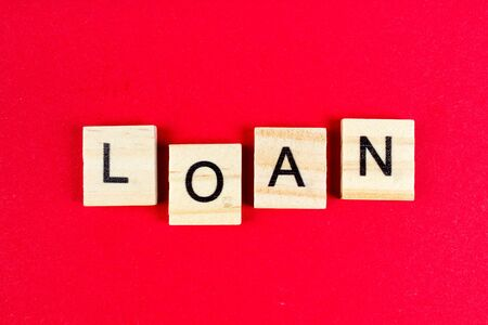 Loan- word composed fromwooden blocks letters on red background, copy space for ad text.