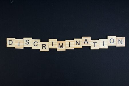 discrimination- word composed fromwooden blocks letters on black background, copy space for ad text.