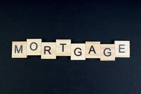 mortgage- word composed fromwooden blocks letters on black background, copy space for ad text.