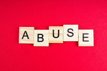Abuse- word composed fromwooden blocks letters on red background, copy space for ad text. Banco de Imagens