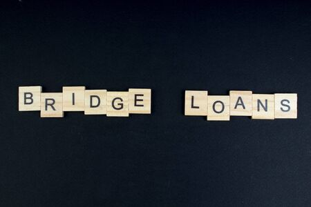 Bridge loans- word composed fromwooden blocks letters on black background, copy space for ad text.