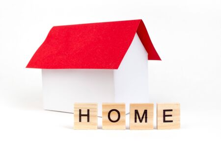 Home- word composed fromwooden blocks letters on red background, layout of a house with a red roof. copy space for ad text.