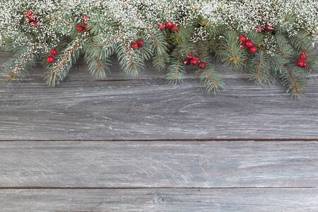 Christmas composition of fir branches and berries of viburnum on a wooden background . Top view with copy space. Banco de Imagens