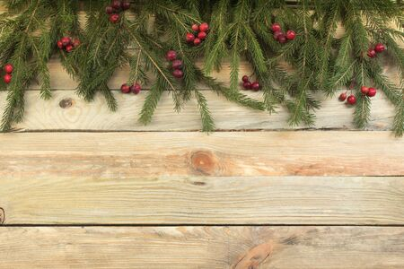 Christmas composition of fir branches and berries of viburnum on a wooden background