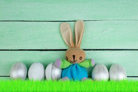 Happy Easter. Colorful easter eggs and rabbit on green grass. Banco de Imagens