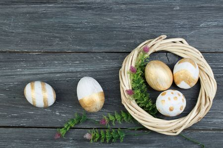 Happy Easter. eggs on wooden table background.. Balls, wreath woven from the vines. Copy space for text. Top view. Banco de Imagens