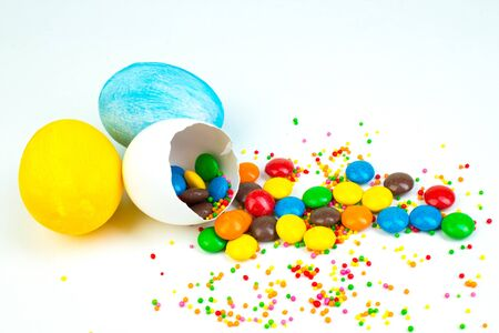 Happy Easter. Broken Easter egg with multi-colored candy decorations. on white background. Colorful eggs Banco de Imagens - 139219181