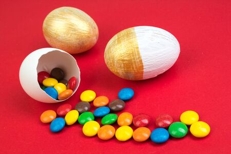 Happy Easter. Broken Easter egg with multi-colored candy decorations. on red background. Colorful eggs