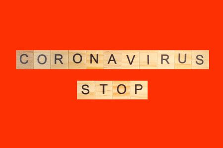 Coronavirus STOP word written on wood block, isolated on red background. top view.