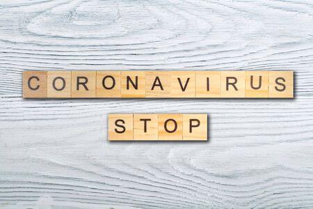 Coronavirus STOP word written on wood block, isolated on wooden table. top view.