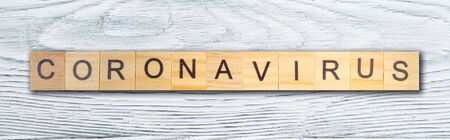 Coronavirus word written on wood block, isolated on wooden table. top view. Mockup for design. banner. panorama, banner.
