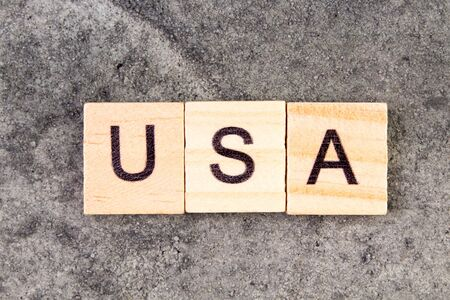 USA word written on wood block, on gray concrete background. Top view. United States of America Reklamní fotografie