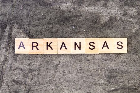 Arkansas word written on wood block, on gray concrete background. Top view.