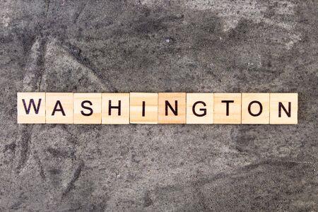 Washington word written on wood block, on gray concrete background. Top view. Reklamní fotografie