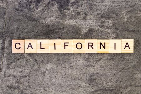 California word written on wood block, on gray concrete background. Top view.