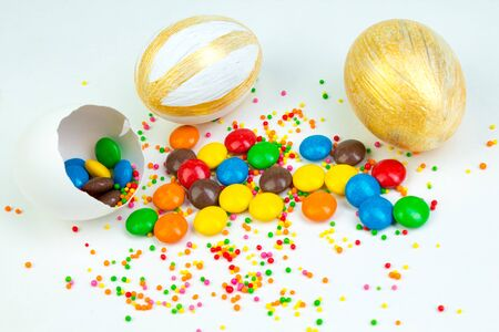Happy Easter. Broken Easter egg with multi-colored candy decorations. on white background. Copy space for text