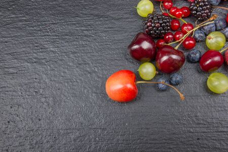 Various summer Fresh berries in a bowl on rustic wooden table. Antioxidants, detox diet, organic fruits. Top view Banco de Imagens