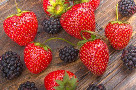 blackberries, strawberrieson wooden table background, spilled from a spice jar. Antioxidants, detox diet, organic fruits Banco de Imagens