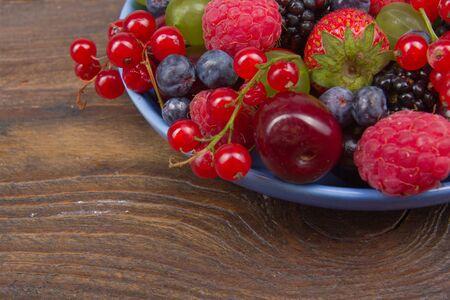 Various summer Fresh berries in a bowl on rustic wooden table. Antioxidants, detox diet, organic fruits. Berries
