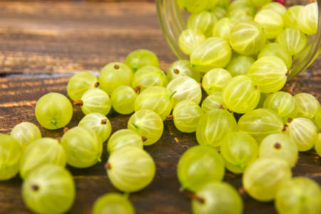 gooseberries on wooden table background, spilled from a spice jar. .Antioxidants, detox diet, organic fruits. Berries