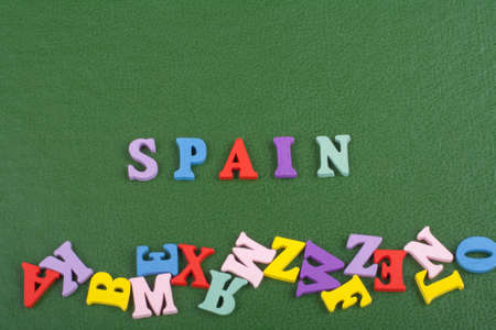 SPANISH word on green background composed from colorful abc alphabet block wooden letters, copy space for ad text. Learning english concept.