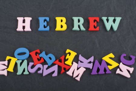 HEBREW word on black board background composed from colorful abc alphabet block wooden letters, copy space for ad text. Learning english concept.