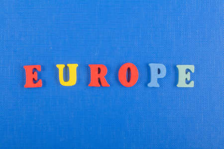 EUROPE word on blue background composed from colorful abc alphabet block wooden letters, copy space for ad text. Learning english concept.