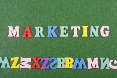MARKETING word on green background composed from colorful abc alphabet block wooden letters, copy space for ad text. Learning english concept. Banco de Imagens