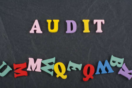 AUDIT word on black board background composed from colorful abc alphabet block wooden letters, copy space for ad text. Learning english concept. Banco de Imagens