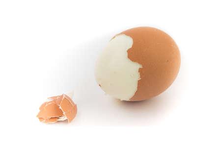Egg with broken shell closeup on white background. Banco de Imagens