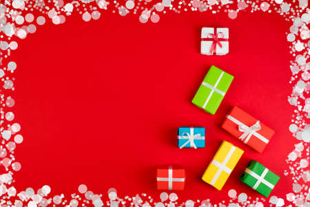 Gift boxes and colorful present for christmas on red background. Top view with copy space. Banco de Imagens