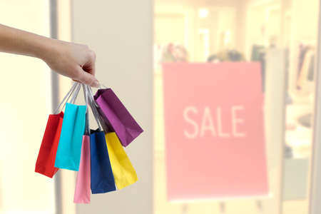 Crop female hand holding colorful paper bags on background of shopping center. black friday, sale