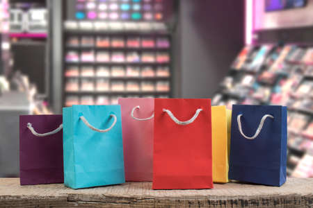 A lot of multi-colored paper shopping bags on a wooden table in a shop. Front view. black Friday