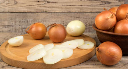 onion in a plate, onion rings on a cutting board. Zdjęcie Seryjne