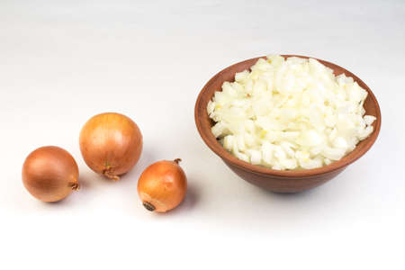 White onion cubes in ceramic bowl isolated on white background.