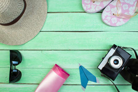 Hat, camera, bag, glasses, sunscreen on a summer wooden background. Top view and copy space.
