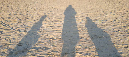 Three human shadows on a yellow brown surface, two adults and one child.