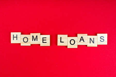 Home loans- word composed fromwooden blocks letters on red background, copy space for ad text.