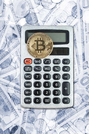 Bitcoin gold coin on calculatoron the background of dollars.. View from above.