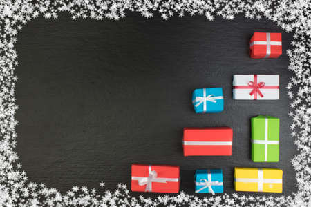 Gift boxes and colorful present for christmas on blackboard. Top view with copy space. Zdjęcie Seryjne