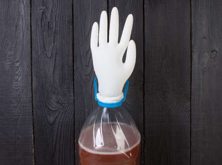 The production of wine. A plastic bottle with a young homemade wine and put on the neck of a rubber glove for fermentation. On a black wooden background.