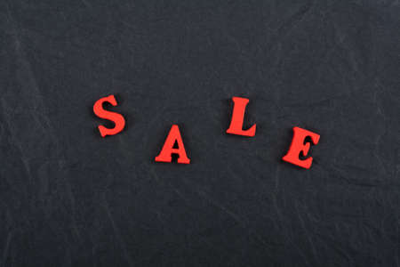 Sale word on black board background composed from colorful abc alphabet block wooden letters, copy space for ad text. Learning english concept. Zdjęcie Seryjne