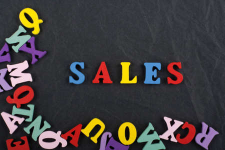 Sales word on black board background composed from colorful abc alphabet block wooden letters, copy space for ad text. Learning english concept.