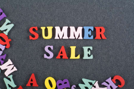 Summer sale word on black board background composed from colorful abc alphabet block wooden letters, copy space for ad text. Learning english concept.