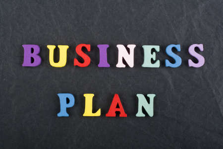 BUSINESS PLAN word on black board background composed from colorful abc alphabet block wooden letters, copy space for ad text. Learning english concept.