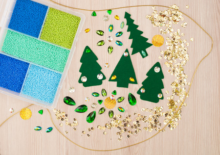 decorative accessories: Christmas card. Beads, cotton textile for needlework and christmas tree made of felt and decorative stones. Hand Made Accessories. Top view Stock Photo