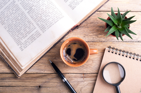 book: Cup of coffee, old open book, succulent, pen, notebook and magnifier on rustic wooden background. Office desk table. Top view. Stock Photo